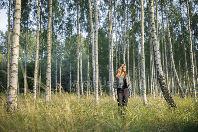 Teenage girl standing in forest, focus on foreground — Stock Photo