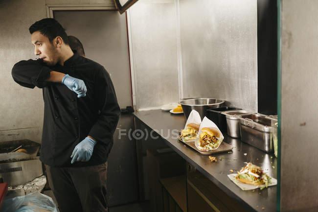 Chef preparando hamburguesas en camión de comida, enfoque selectivo - foto de stock