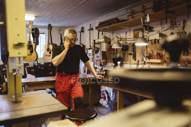 Craftsman talking on phone in guitar making workshop — Stock Photo