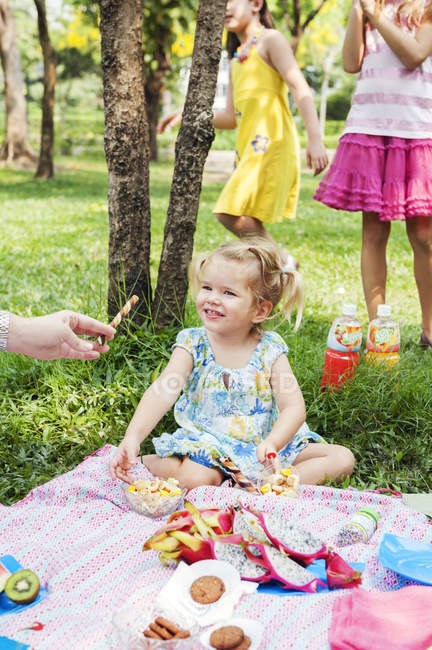 Mother giving daughter candy at birthday picnic — стокове фото