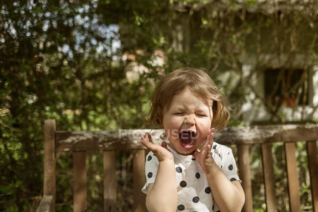 Piangere ragazza seduta in cortile, concentrarsi sul primo piano — Foto stock