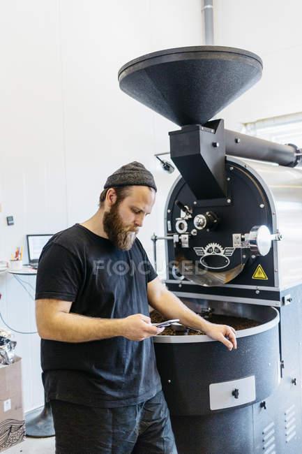 Людина перевірки мобільний телефон поруч з кавової машини для смаження — стокове фото