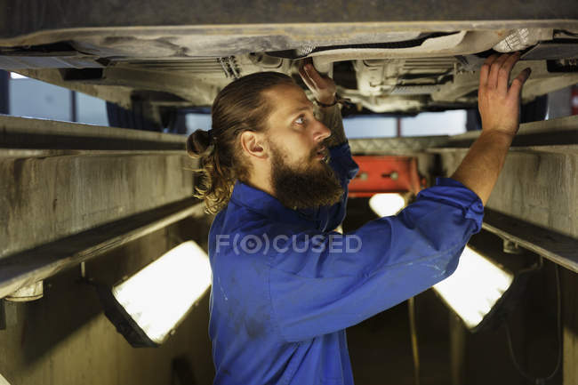 Mechanic working on car in workshop, selective focus — стоковое фото