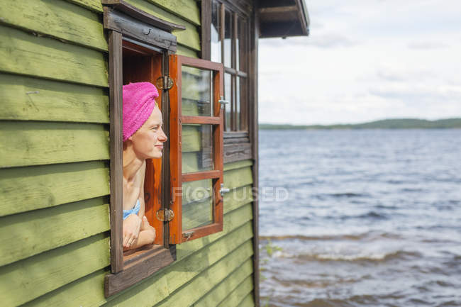 Mid adult woman looking out window of sauna — Stock Photo