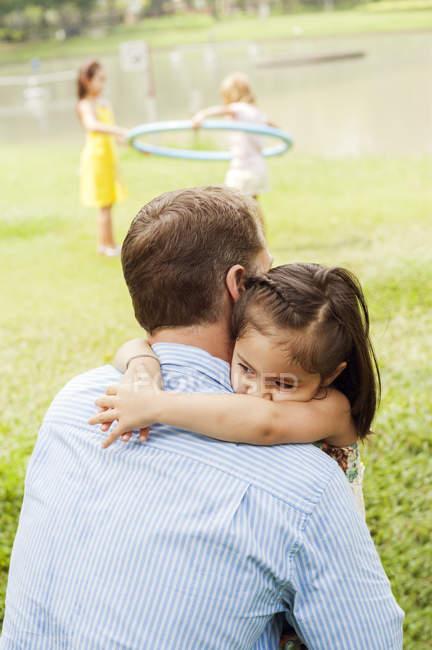 Pai e filha que abraçam no parque, foco no primeiro plano — Fotografia de Stock