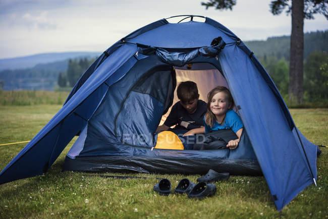 Enfants dans la tente dans la prairie, se concentrer sur le premier plan — Photo de stock