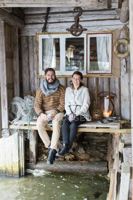 Jeune couple assis sur une table en bois — Photo de stock