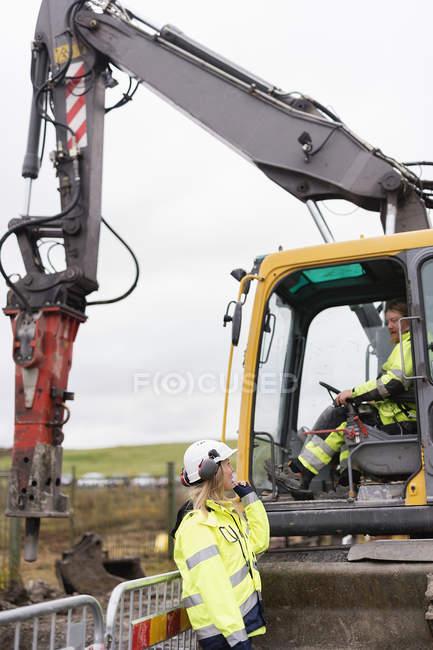 Женщина, говорят человеку внутри земли двигателем на строительной площадке — стоковое фото