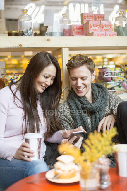 Man and woman using smart phone in cafe, focus on foreground — Stock Photo