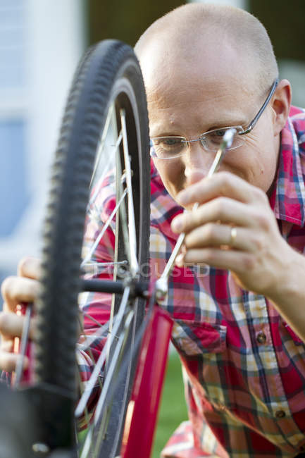 Man fixing bicycle, differential focus — Stock Photo