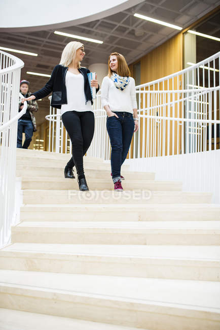 Low angle view of two women walking down stairs — Stock Photo