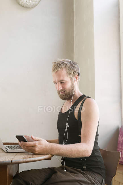 Man with earphones sitting at table and using smartphone — Stock Photo
