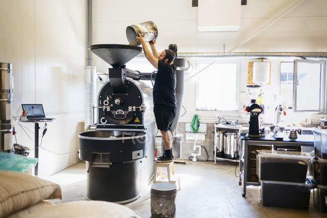 Man pouring coffee beans into roasting machine — Stock Photo