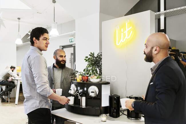 Мужчины за кофе в офисе, коллеги во время кофе-брейка — стоковое фото