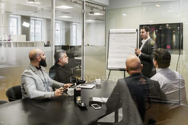 Hommes discutant de projet lors d'une réunion d'affaires au bureau — Photo de stock