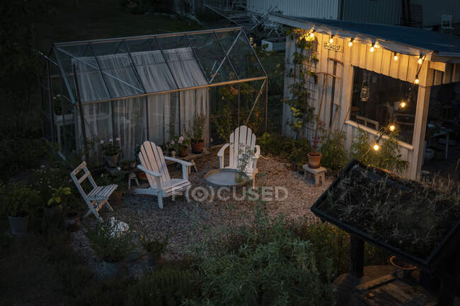 Deck chairs by greenhouse in backyard at sunset, high angle view — Stock Photo