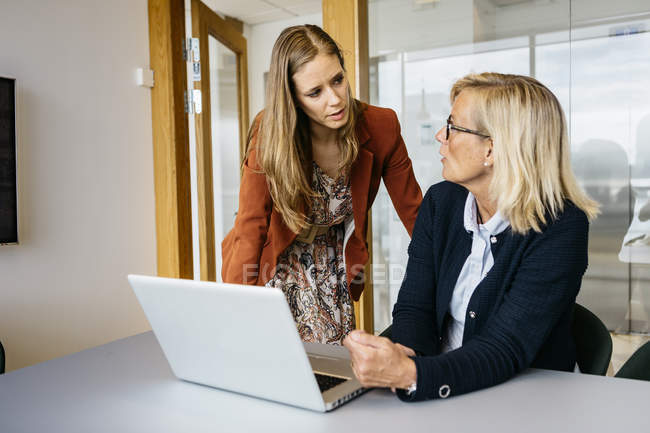 Businesswomen using laptop, focus on foreground — Stock Photo