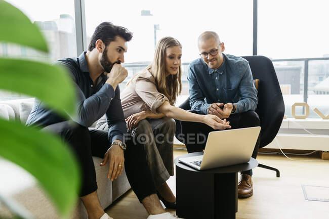 Сфокусовані молоді ділові люди використовують ноутбук у офісі — стокове фото
