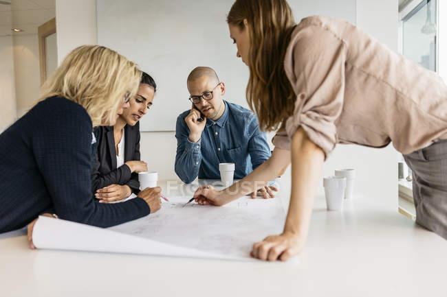 Imprenditori che guardano i piani durante la riunione — Foto stock