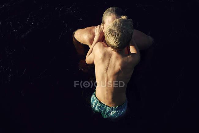 Підвищена думка матері і сина купання в озері — стокове фото