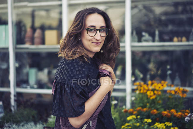 Smiling young woman wearing glasses in garden — Stock Photo