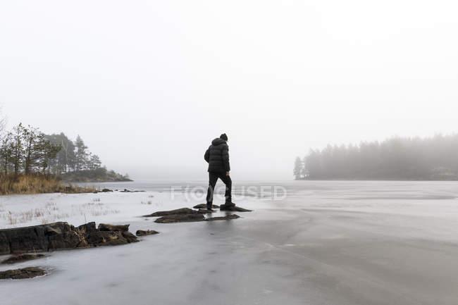 Man on rocks in frozen lake in Lotorp, Sweden — стоковое фото