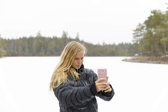 Young woman taking selfie in front of a lake in the snow — Stock Photo