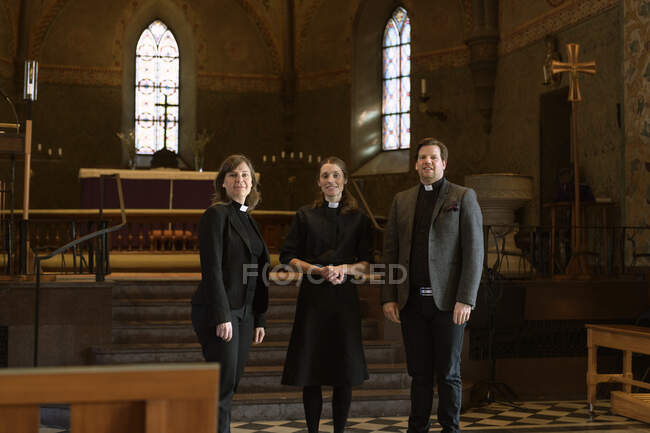 Portrait of priests in church standing together and looking at camera — Stock Photo