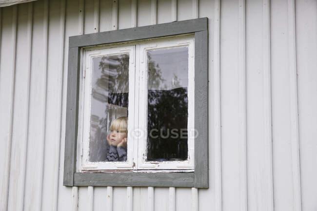 Cute little boy in window of house — Stock Photo