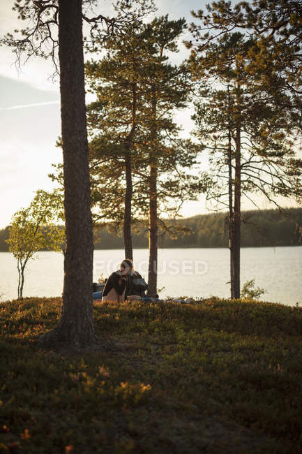 Young woman reading at sunset by Lake Norra Bredsjon, Sweden — Stock Photo