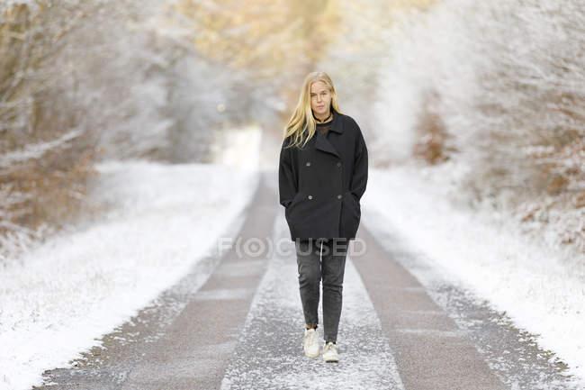 Jeune femme marchant sur la route enneigée — Photo de stock
