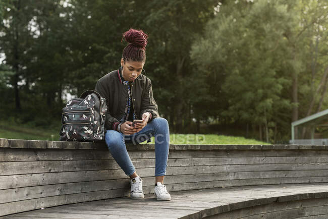 Teenage girl sitting and using smartphone in park — Stock Photo