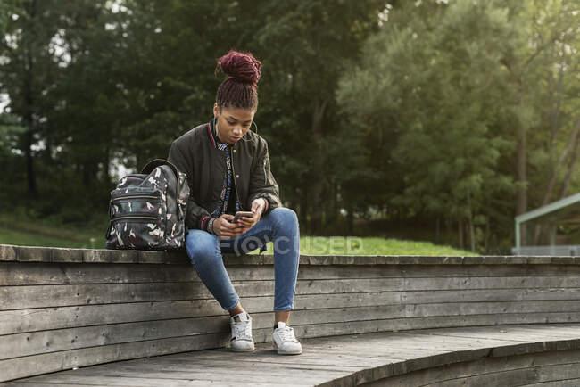 Une adolescente assise et utilisant un téléphone intelligent dans un parc — Photo de stock
