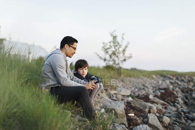 Pai e filho usando um telefone inteligente na grama — Fotografia de Stock