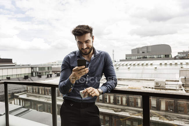 Young man looking at cell phone on balcony — Stock Photo
