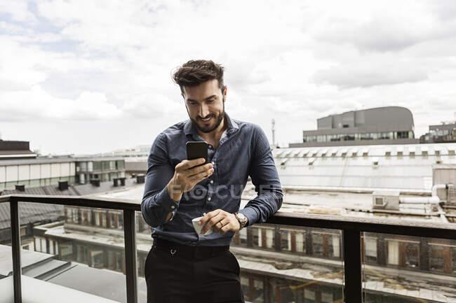 Jeune homme regardant un téléphone cellulaire sur un balcon — Photo de stock