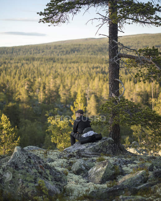 Man sitting on rock in Tofsingdalen Nature Reserve in Sweden — Stock Photo