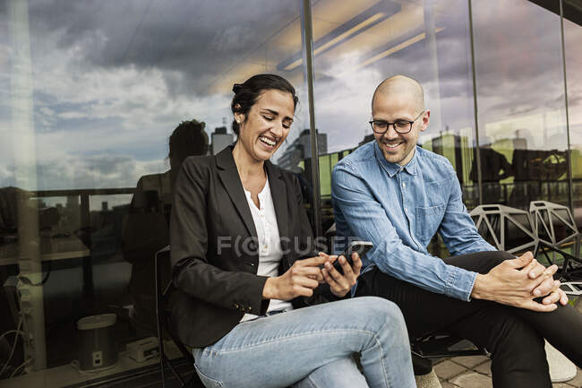 Friends laughing while looking at cell phone — Stock Photo