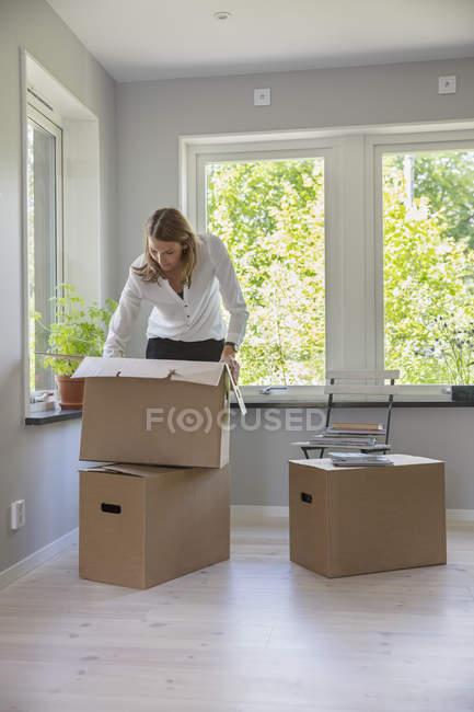 Mulher desempacotando caixas de papelão na casa nova — Fotografia de Stock