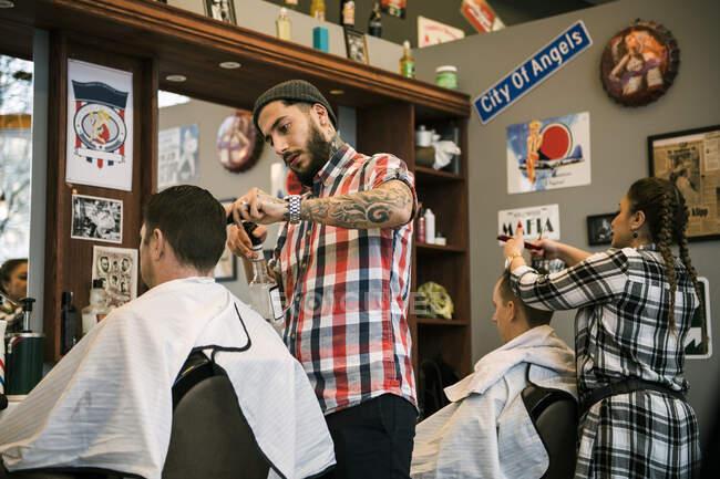 Friseure schneiden Kundenhaare im Friseursalon — Stockfoto