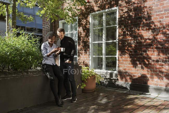 En souriant de jeunes amis debout à l'extérieur de la maison et en utilisant ensemble un téléphone intelligent — Photo de stock
