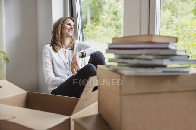 Mujer sentada en la ventana detrás de las cajas de cartón - foto de stock