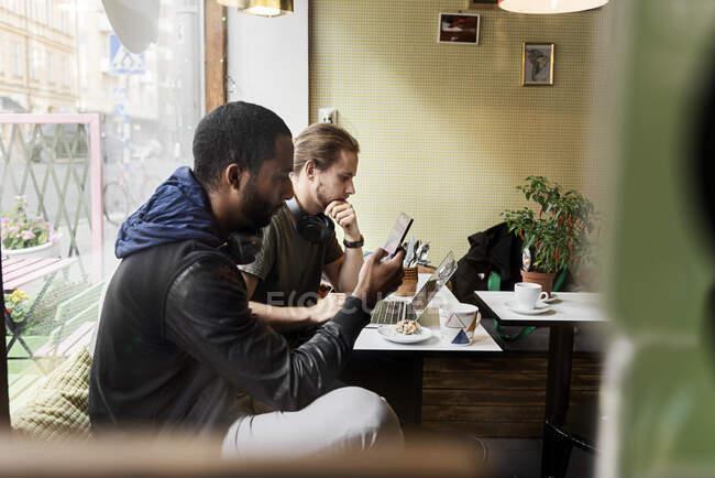 Vue latérale de jeunes hommes assis et utilisant des dispositifs numériques dans un café — Photo de stock