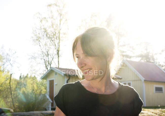 Woman smiling in sunlight while standing outdoors — Stock Photo