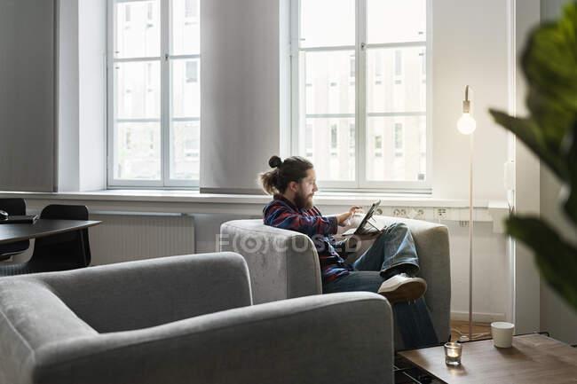 Чоловік сидить у кріслі і за допомогою планшета ПК за лампою — стокове фото