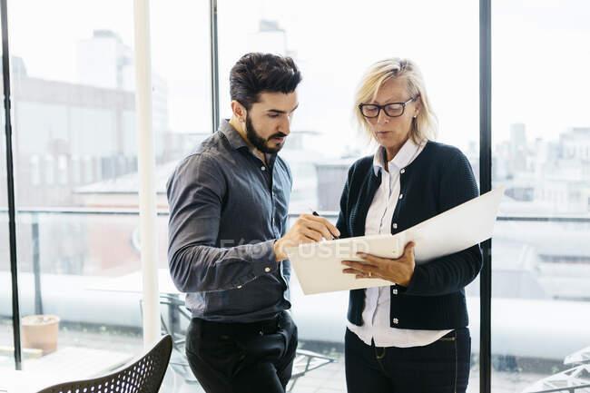 Бізнесмени, які обговорюють роботу в офісі. — стокове фото