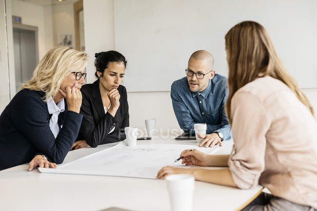 Businesspeople looking at plans during meeting — Stock Photo
