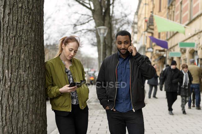 Coppia utilizzando smartphone sul marciapiede, messa a fuoco selettiva — Foto stock