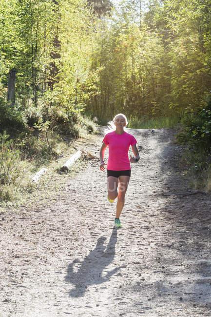 Женщина, бегающая в лесу, избирательный фокус — стоковое фото