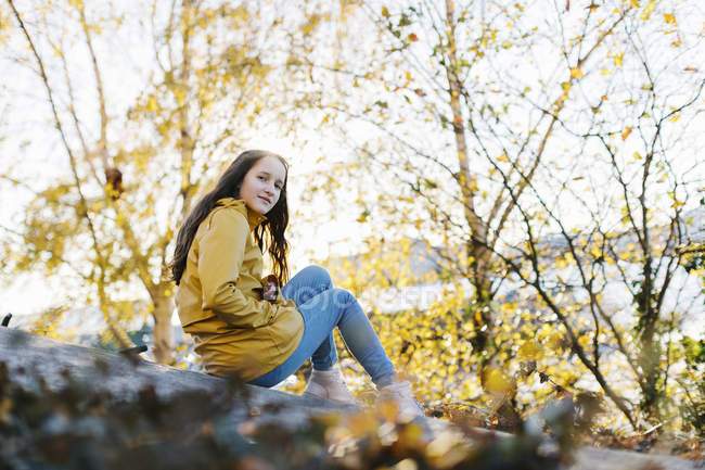 Girl wearing yellow raincoat sitting by trees — Stock Photo